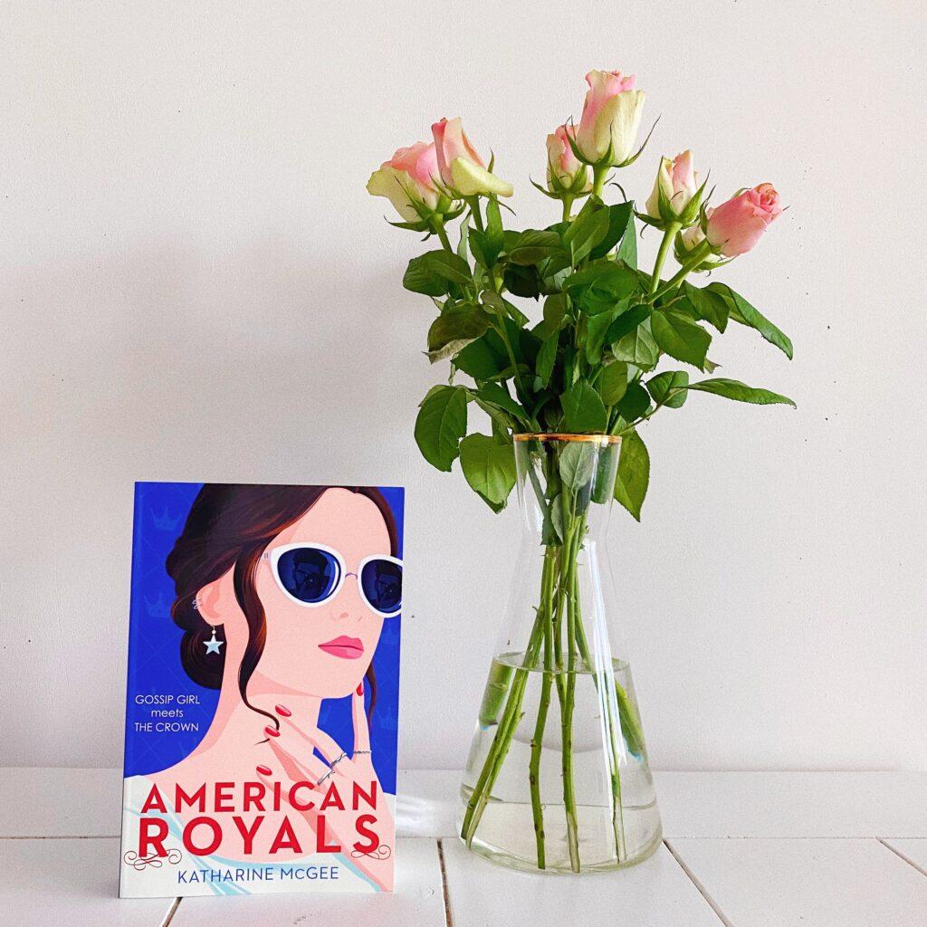 American Royals boek naast een vaas met rozen.