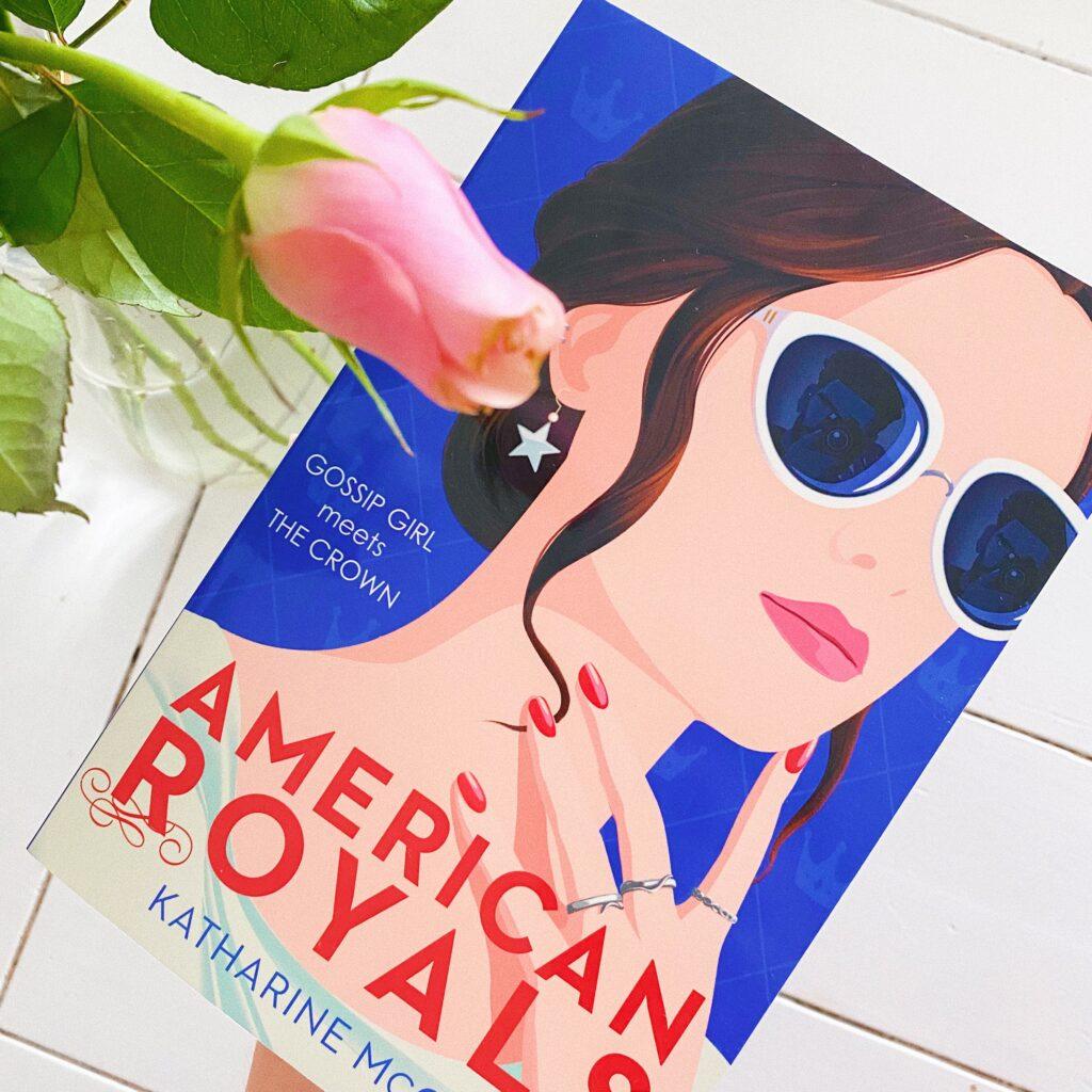 American Royals boek naast een vaas met bloemen.
