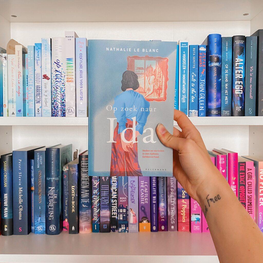 Foto van Op zoek naar Ida, Nanouk houdt het boek vast en op de achtergrond zie je haar boekenkast.