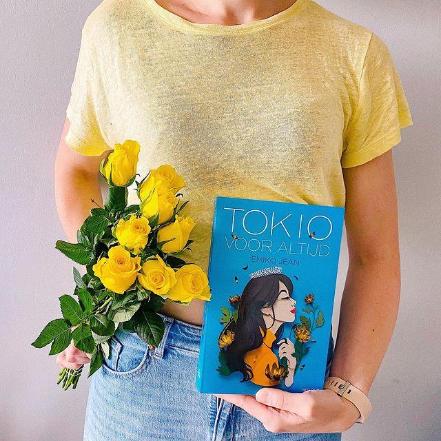 Nanouk staat in een geel shirt (hoofd niet zichtbaar), linkerhand het boek Tokio voor altijd, rechterhand bos gele rozen.